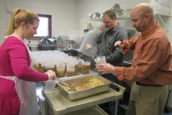 School district superintendent John Sanville (right) helped ladle soup into containers at Hillendale.