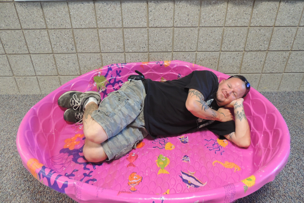 Tommy Lawrence, Blackridge Elementary School's head custodian, poses for a picture from within a plastic pool at the school. (Blackridge Elementary)