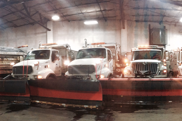 Snowplows sit in the Public Works Building lined up, ready to go. (West Jordan City).