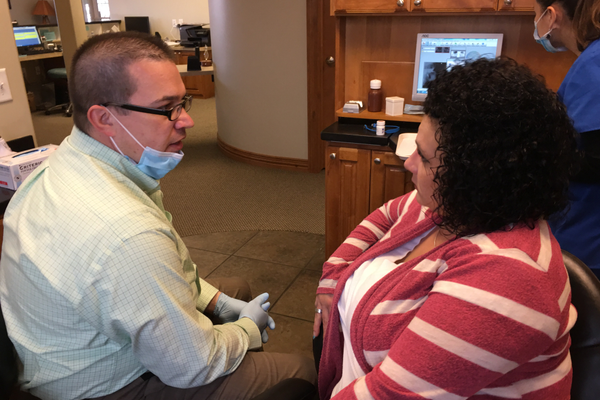After looking at an X-ray, dentist Doug Hansen explains how he will reconstruct Patricia Lochhead's mouth. Silver Summit Dental is gifting the dental work to Lochhead, a single mother with only nine teeth. (Tori La Rue/City Journals)