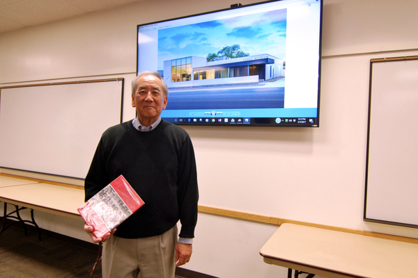 Rick Okabe poses with a book about the children of the Topaz Internment Camp in front of an image of the new Topaz Museum, to open in spring 2017. (Keyra Kristoffersen/City Journals)