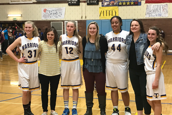 Warriors seniors Katie Burgess, Maizy Burbank, Zae Patane and Mari Hasebi stand with their coaches after their final home game. (Greg James/City Journals)