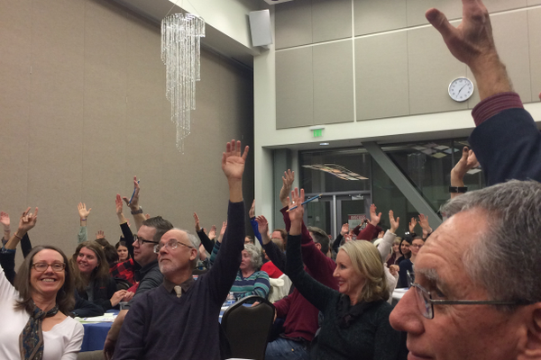 The crowd raises its hands when asked if anyone had learned something that night. (Marina McTee/City Journals)