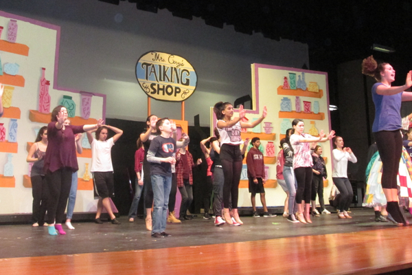 The large cast runs through their steps under the direction of a student choreographer.