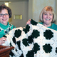 Peggy Manning (right) shows off the afghan she won, handmade by Joanne Guzowski (left)