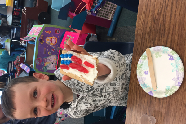 Kindergartner Hank Tuttle makes an American flag on a graham cracker as part of the Kindy 500's activities. (Julie Slama/City Journals)