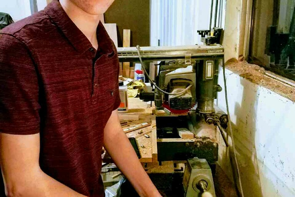 Peyton Williams poses for a picture while creating a pen in his workshop. Williams wrote a memoir, partially about pen making, that reached Gold Key status in the longest-running creative teen contest in the United States. (Peyton Williams)