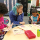 Cassie Green helps her children prepare their math games. (Jet Burnham/City Journals)