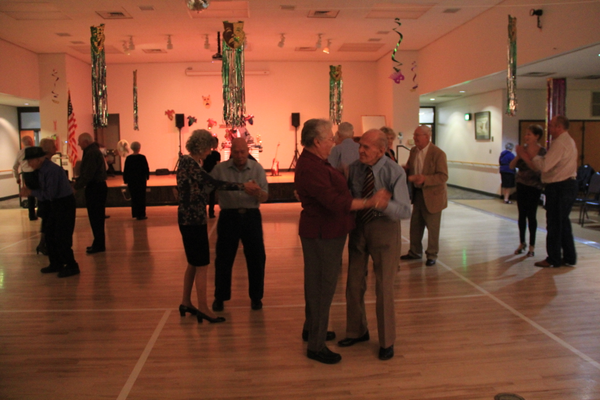 Karl Tinggaard (center, in blue) dances with a partner at the Murray Heritage Senior Center, with others who come every week to participate.