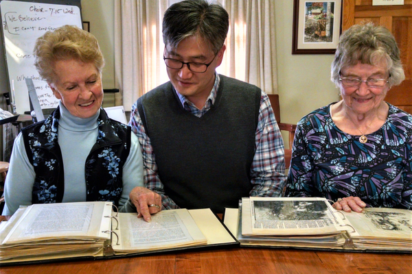 From left: Lydia Akerman, the Rev. Hu Ju Lee and Alma Rigler look over scrapbooks Alma Rigler compiled over the years chronicling the Landenberg UMC's history. (Photo by Natalie Smith)