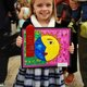 Cali McArthur, first-grader from American Preparatory Academy in Draper, shows off the piece that won her second place. (Keyra Kristoffersen/City Journals)