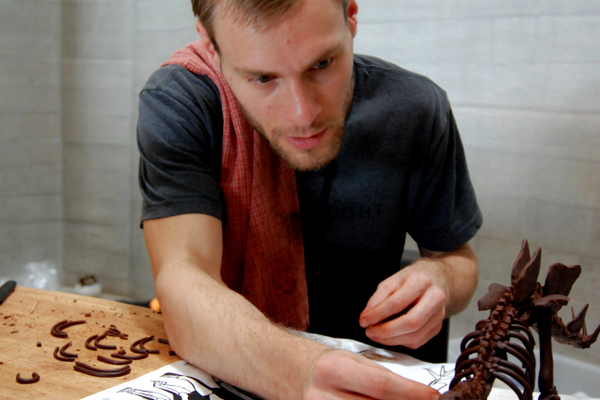 While making of a chocolate stegosaurusStegosaurus, Alex Walton fits a rib in place. (Keyra Kristoffersen/City Journals)