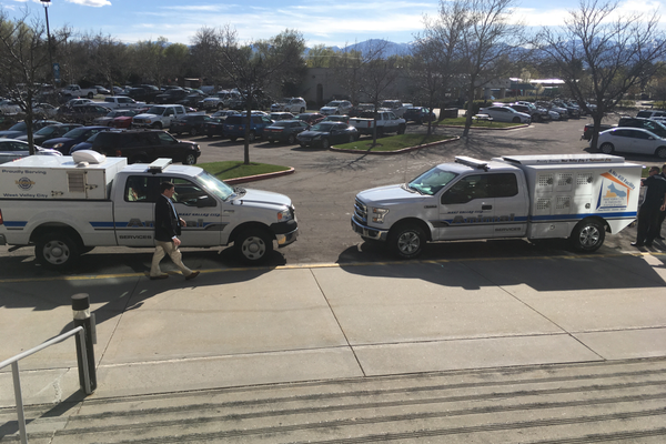 Sam Johnson, director of strategic communications, walks past the two animal service vehicles. The newly built truck (right) is replacing the older version (left). (Travis Barton/City Journals)