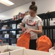 Morgan Byrne fills a bag with food. The bags of food go to various agencies who distribute the food to kids who will need to eat on the weekend. (Travis Barton/City Journals)