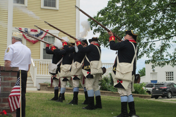 Members of the Henry Knox Color Guard fire their rifles after the wreath-laying ceremony at Town Hall