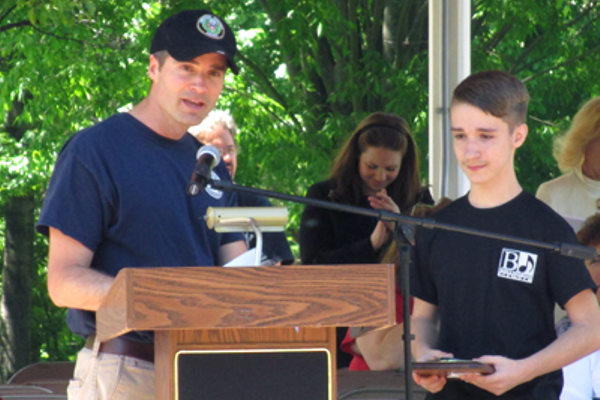 Sam Cowell, left, of the Memorial Day Committee, introduces Carson Saponaro, who won an essay contest on the meaning of the holiday. Saponaro is a Grade 7 student in Robin Ambler's English class at the Memorial Middle School.