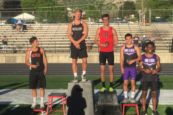 Jake Boren stands on the podium after winning 200-meter dash. (Swede Robinson/ Highland High)