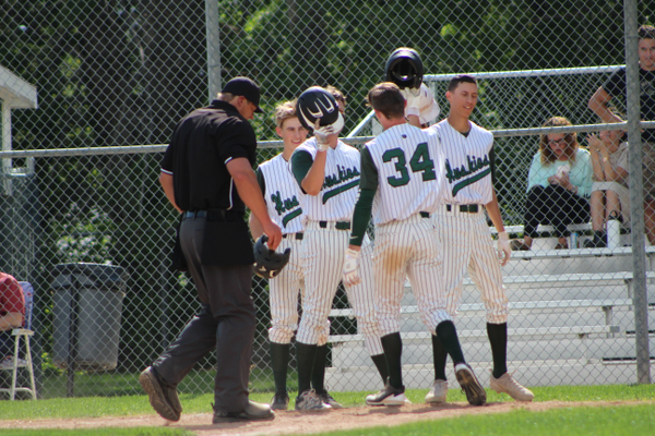 Teammates celebrate with senior Brendan Begley after his three-run home run. (Travis Barton/City Journals)