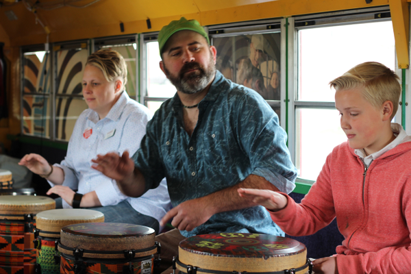 Librarian Jackie Standing, drumming facilitator Nels Anderson and a Kearns teen beat on drums during a Kearns Library event. Anderson teaches various groups how to play West African drums from his DrumBus, a mobile classroom. (Tori La Rue/City Journals)