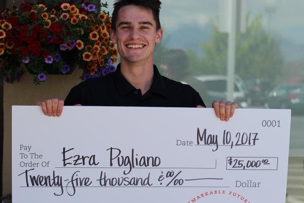 Ezra Pugliano smiles while holding the giant $25,000 scholarship check Chick-fil-A granted him on May 10. The sophomore financial advising major at Utah Valley University was selected as a scholarship recipient out of thousands of applicants. (Tori La Rue/City Journals)
