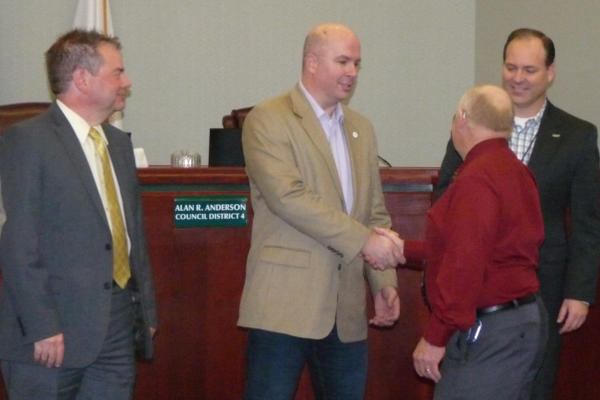 David Newton shakes hands with city Councilman Zach Jacob, while councilmen Alan Anderson and Chad Nichols look on. (Carl Fauver)