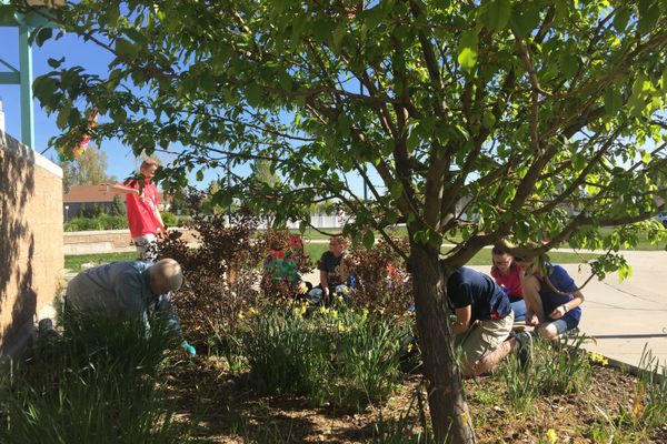 Terrie Kenner, enrichment specialist at Herriman Elementary, gardens with students on a May afternoon. (Katie McEwen/Herriman Elementary)
