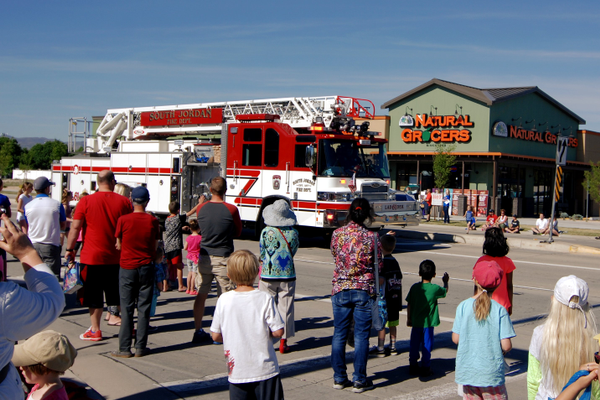 Families cheer for the South Jordan Fire Department as they toss candy during the parade. (Keyra Kristoffersen/City Journals)