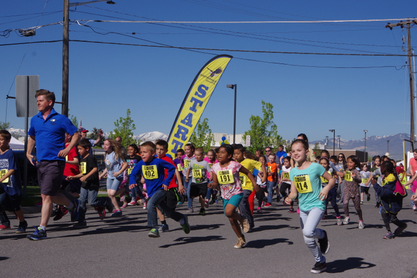 East Midvale Principal Justin Pitcher leads the students on a 1-mile fun run to help raise funds for the school. (Julie Slama/City Journals)