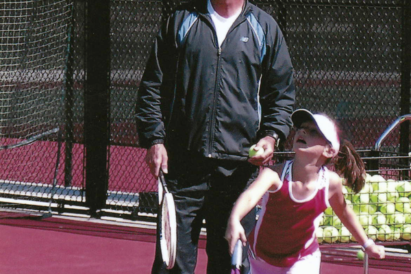 John and student Sophia Nielsen watch the tennis ball as Nielsen completes her follow through (Sylvia Nielsen)