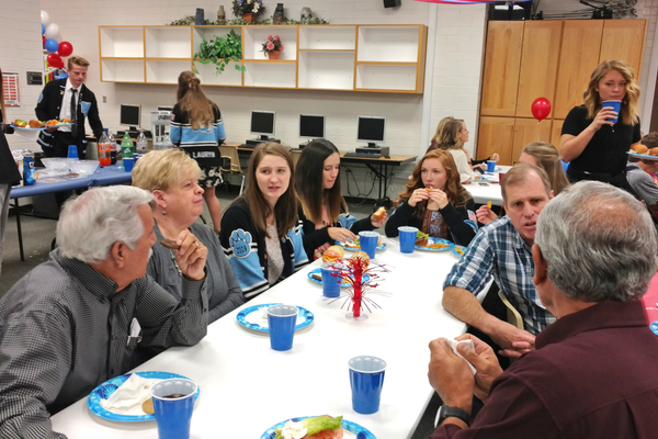 Students visit with veterans and their families at a private luncheon. (Jet Burnham/City Journals)