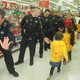 Police officers store employees and event organizers high-five the children as they arrived