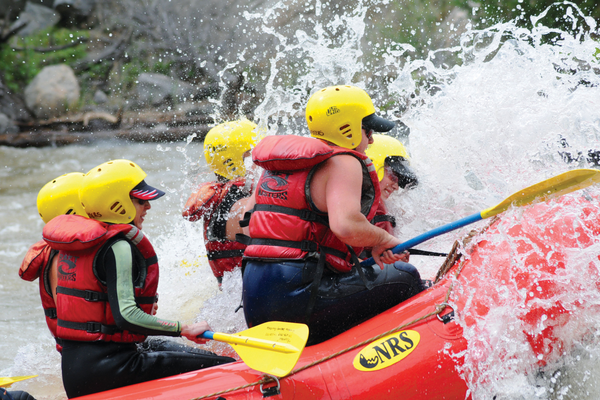 Water splashes up from the rapids, dousing rafters in the front of the vessel. Photo courtesy of Raft Masters.