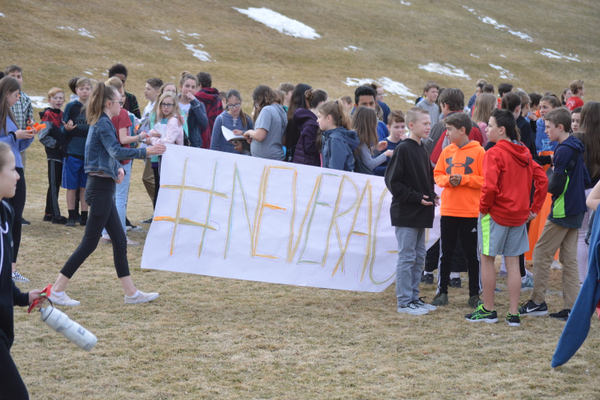 "Students at Churchill Jr. High hold a banner that says, ""#NeverAgain."" (Justin Adams/City Journals)"