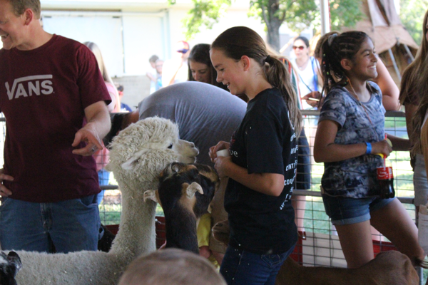 Kids, teenagers and adults stepped inside the petting zoo ring to pet the goats, ducks and chickens found in there. (Travis Barton/City Journals)