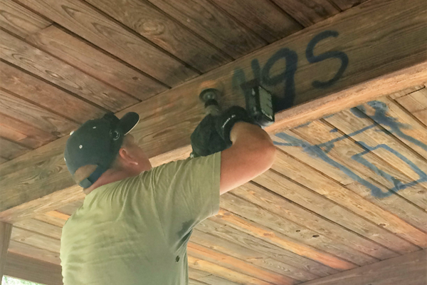 A volunteer uses a grinder to sand off graffiti on one of the roof supports.