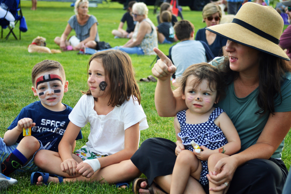 A family sits on the grass as they enjoy some of the live music.