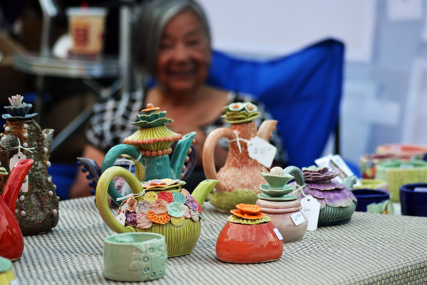 Victoria Acoba shows off her hand-made ceramic teapots.