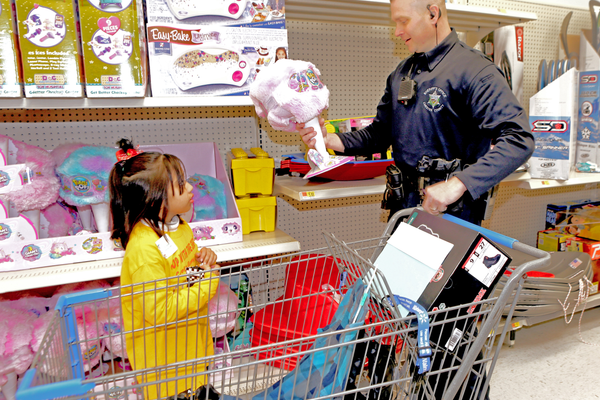 A deputy and student examine a toy that the helper described as looking like cotton candy.