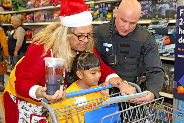 Anne Hamilton, who is one of the early founders of Shopping with the Sheriff, greets a shopper and deputy on Saturday.