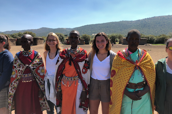 Emma Scopa and Emily Chmela stand with some of the women of the village of Maasai Mara, Kenya.(Mike Scopa photo)