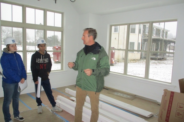 Robert Duffy in the living room of a home under construction, with the property's original stone farmhouse behind him. The historic home will be renovated.