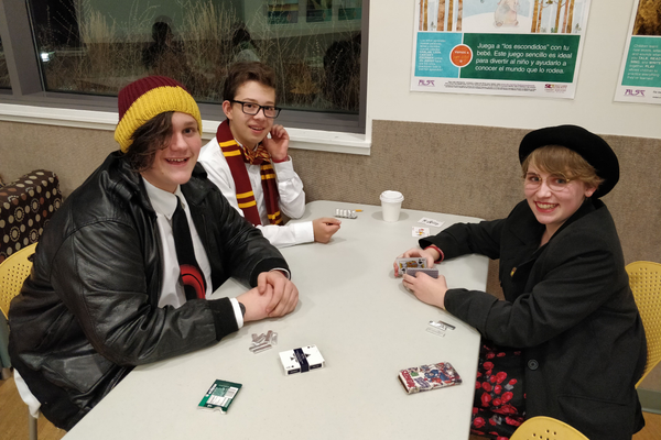A few kids play cards outside the Yule Ball.
