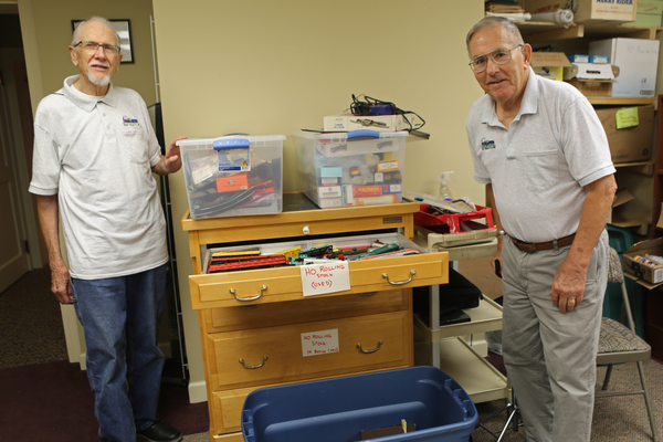 From left, Ed Crowell and Dick Fowler stand beside recently acquired boxes of trains.