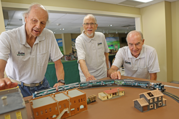 From left, Bob Philhower, Ed Crowell and Fred Crotchfelt gather around the Eagles train, which they acquired over the past several months.