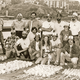 "PREPPING FOR THE FIREWORKS SHOW: Randy's dad, Walt Liebig, standing at left, and other volunteers get ready for the 1978 Fireworks display at the SC pier. Randy is in the front row to the left of ""Miss 4th of July"" Randy's brother Ron is front row at right."