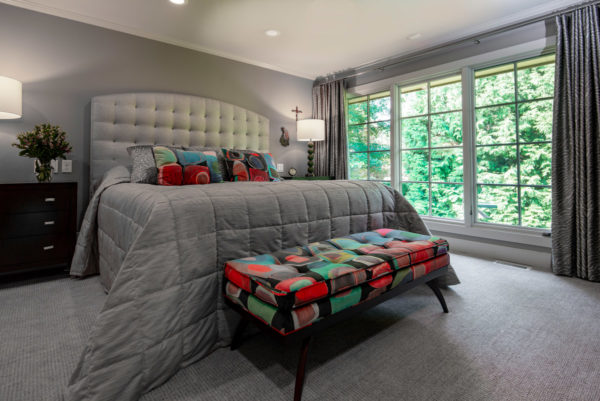 Large bed, colorful bench, large windows