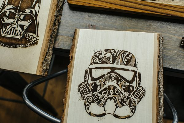 Two wood engravings, Darth Vader on left, storm trooper on right