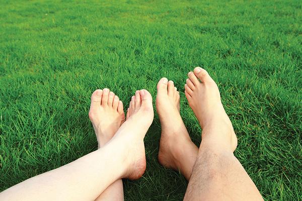Bare Feet on Organic Green Grass Lawn