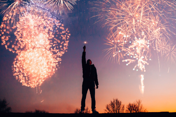 man's silhouette with fireworks in sky