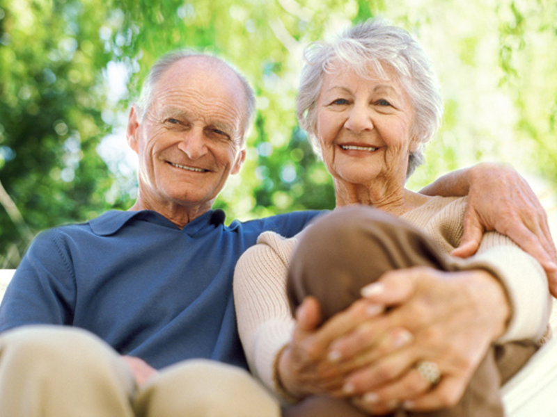 Elderly couple smiling and sitting outside